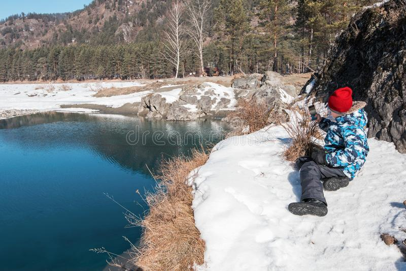 在海岸河的年轻男孩照相 免版税库存照片