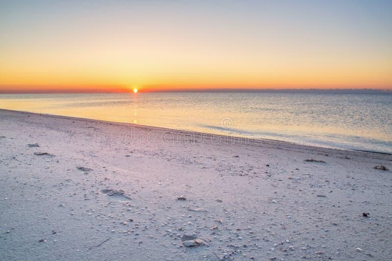 在海岸的太阳日出,在海滩的脚印 图库摄影