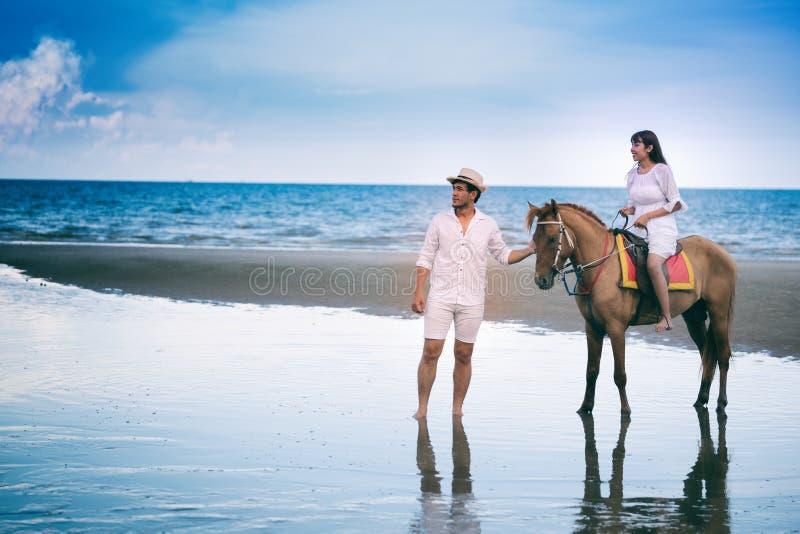 在海岸的幼小夫妇骑乘马 免版税图库摄影