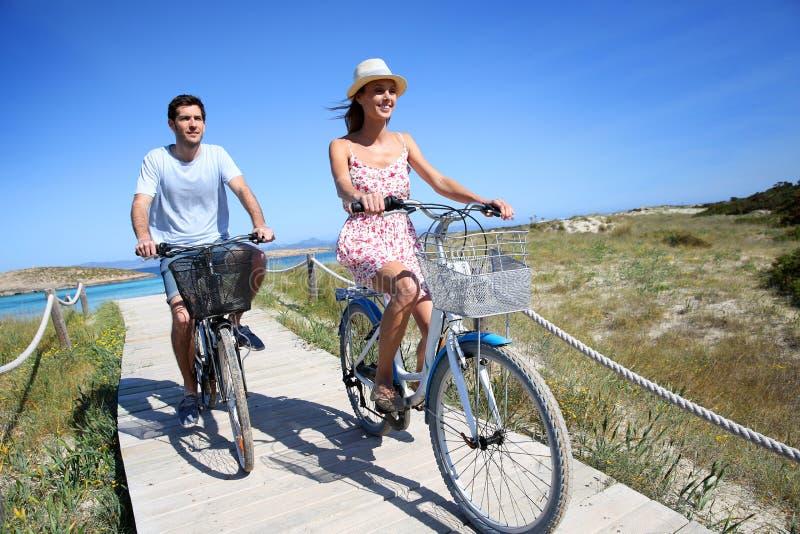 在海岸的愉快的夫妇骑马自行车 库存图片
