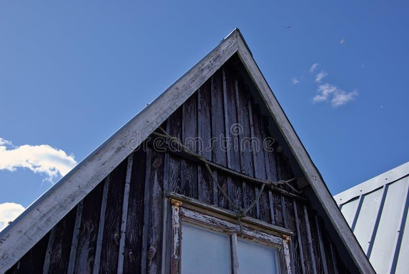 在海岸的美丽的黑渔小屋 库存照片