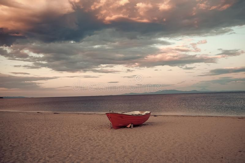 在海岸的Fishermens小船,在日落的沙子与背景的horisont海 海背景有波浪和天空的 免版税库存照片