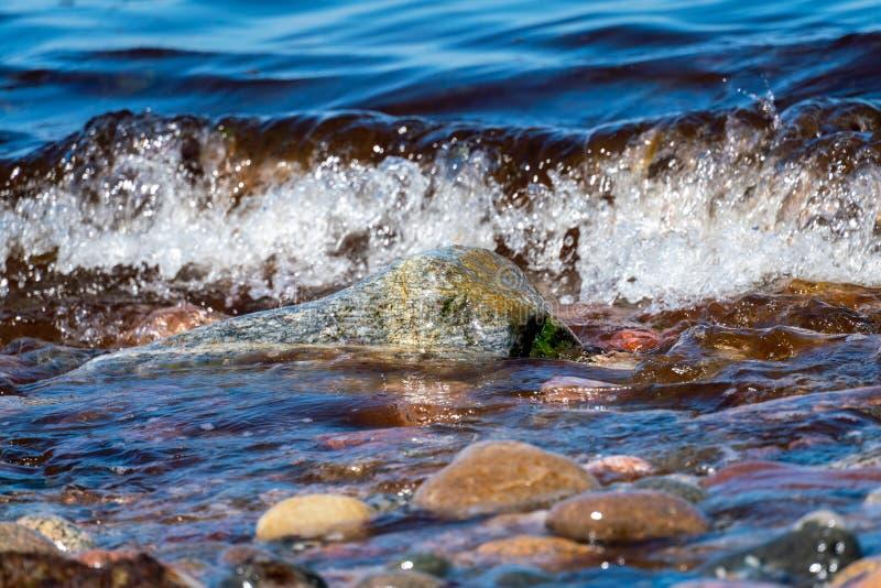 在海岸线的色的小卵石有水和波浪的 免版税库存照片