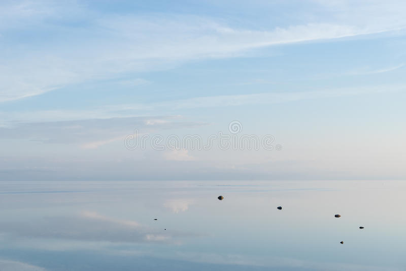 在海岸,桃红色云彩,在水的蓝天反射的晚上阳光 海滩海岸线展望期山夏天 海边自然环境 库存照片