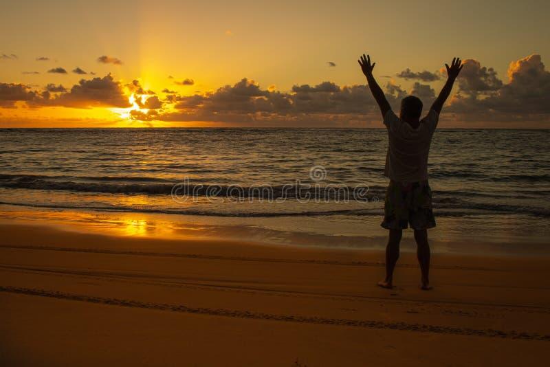 在海岸A人的日出传播他的胳膊到天堂 温暖的口气风景  图库摄影