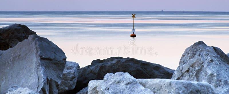 在海平面的日出与线、岩石和浮体 免版税库存图片