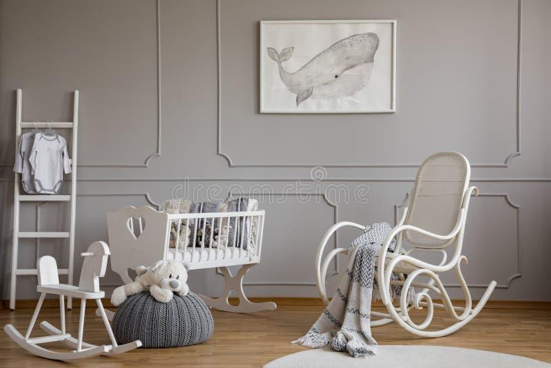 在海报的灰鲸科在与白色木摇椅、摇马、小儿床和斯堪的纳维亚梯子的优等的婴孩室内部, 免版税图库摄影