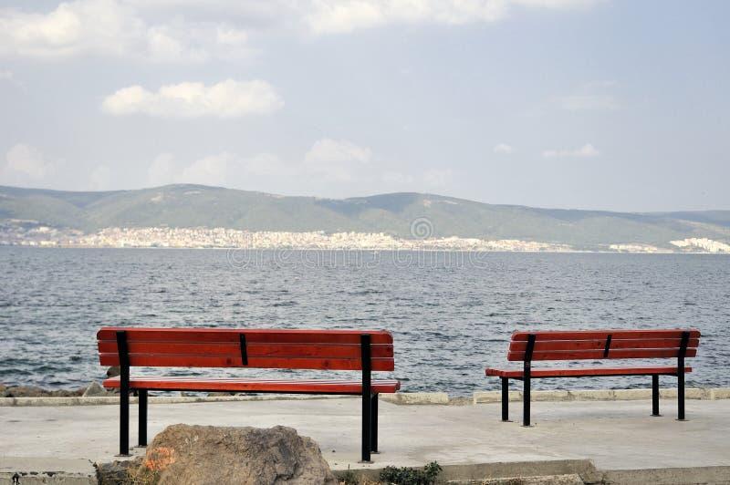 在海旁边的偏僻的两benchs 免版税图库摄影