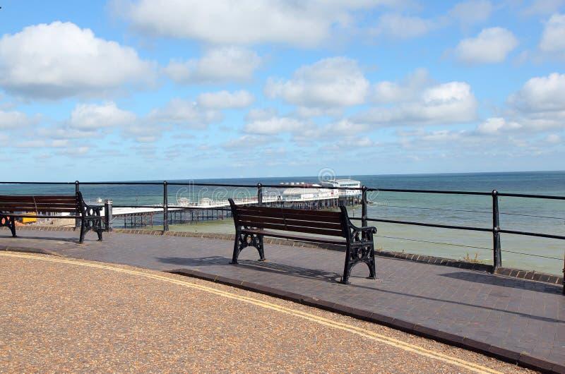 在海旁边的空的长凳。 免版税库存图片