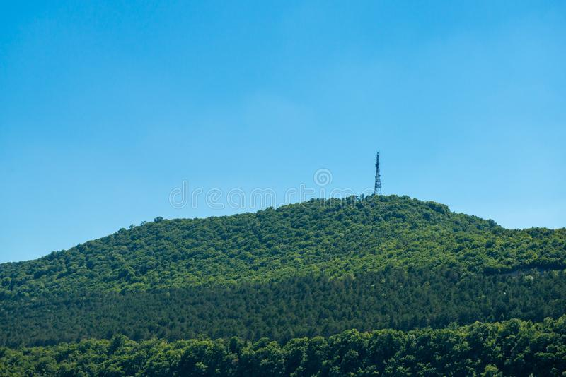 在海旁边的绿色山有在上面的无线电铁塔的 库存图片