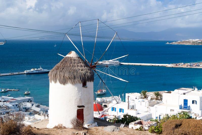 在海景的风车在米科诺斯岛,希腊 在山的风车由天空的海 与风帆和秸杆的被粉刷的大厦 免版税库存图片