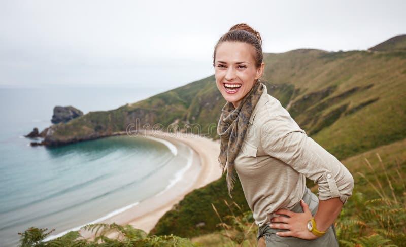 在海景风景前面的愉快的冒险妇女远足者 库存图片