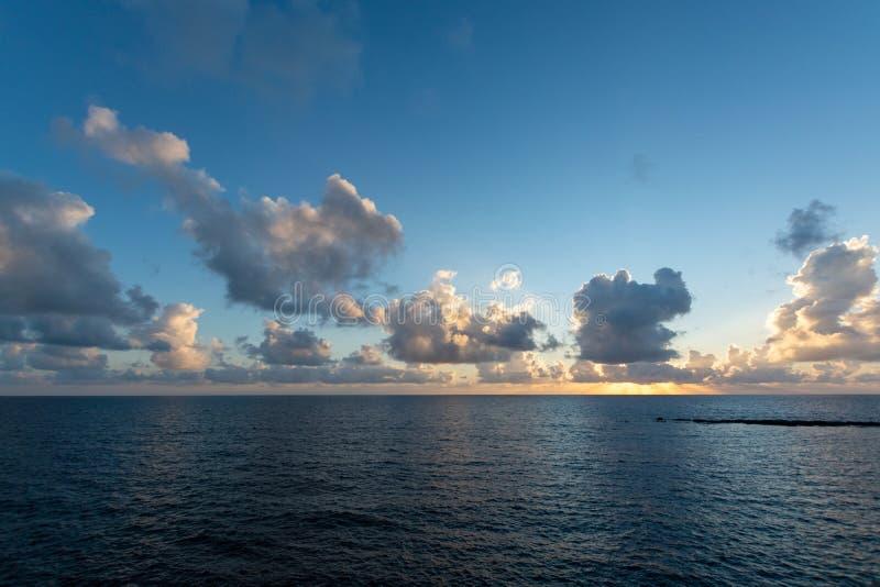 在海水的剧烈的日落与灰色云彩和太阳光 免版税库存图片