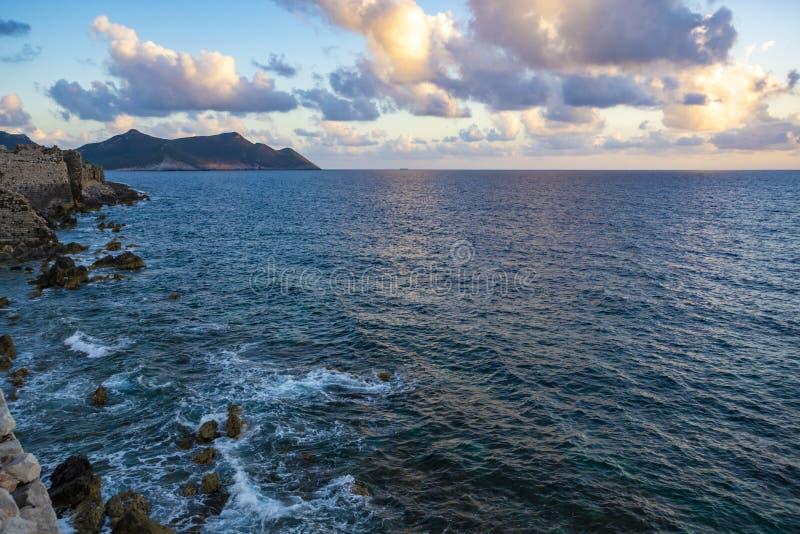 在海水的剧烈的日落与灰色云彩和太阳光 库存图片