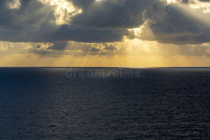 在海水的剧烈的日落与灰色云彩和太阳光 免版税库存照片