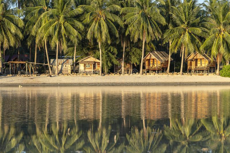 在海水被反射与可可椰子树和木平房的美丽的海湾 热带沙滩,绿色棕榈叶 免版税库存图片