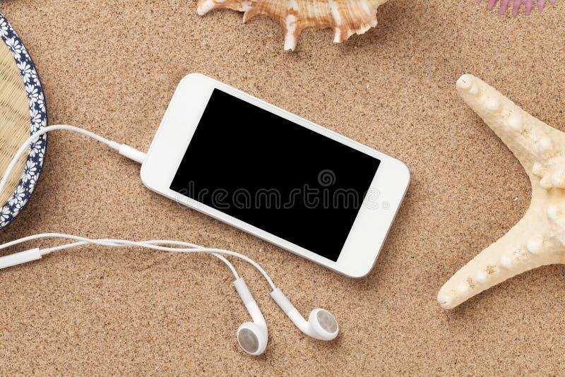 在海沙的智能手机与海星和壳 免版税图库摄影
