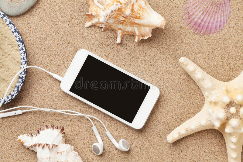 在海沙的智能手机与海星和壳 库存图片