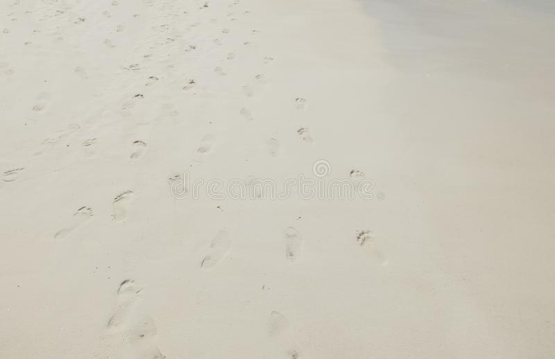在海沙背景纹理的脚邮票 库存图片