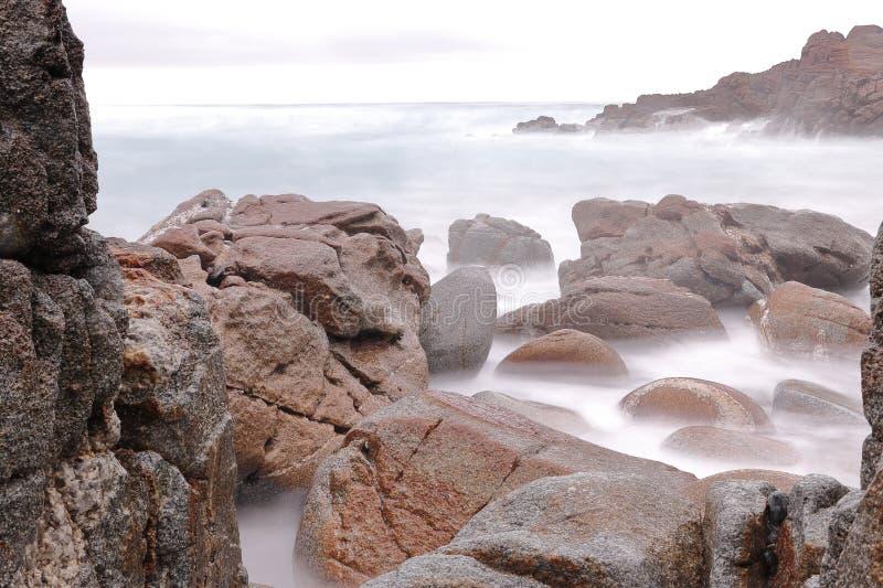 在海波浪力量腐蚀的海岸的岩石  图库摄影