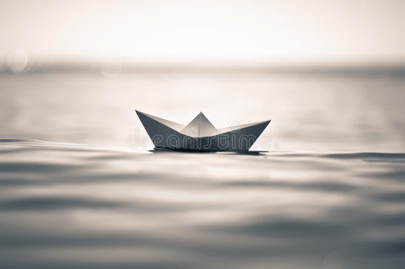 在海波浪的Aper小船 纸小船的被定调子的图象 库存照片