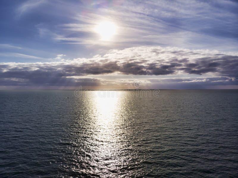 在海洋上的鸟瞰图,有多云淡色色的风景天空和太阳光芒的在一个热的夏日击中水 免版税库存照片
