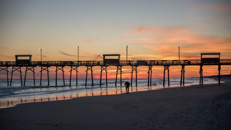 在海洋海岸的五颜六色的日落与码头和照片剪影  库存照片