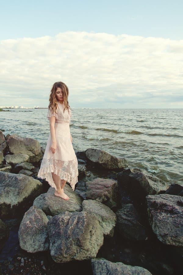 在海洋海岸,浪漫秀丽画象的美女佩带的boho礼服 图库摄影