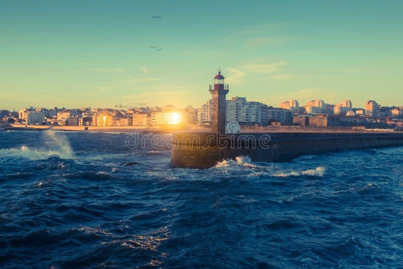 在海洋灯塔的美好的日落在波尔图海岸  库存图片