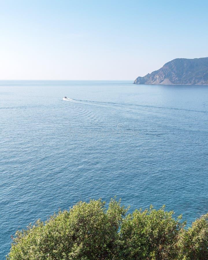 在海洋的一条小船 与有些峭壁的大海在背景和绿叶中在前景 意大利,五乡地 ?? 库存照片