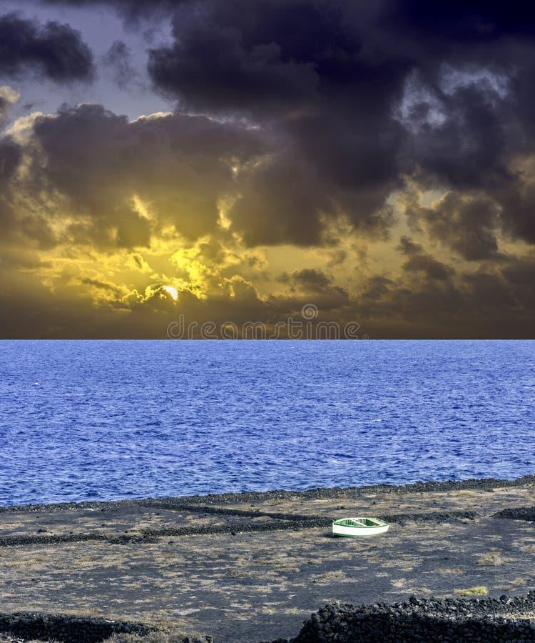 在海洋的剧烈的日出在与空的小船的风暴前- Los Cocoteros 免版税库存图片