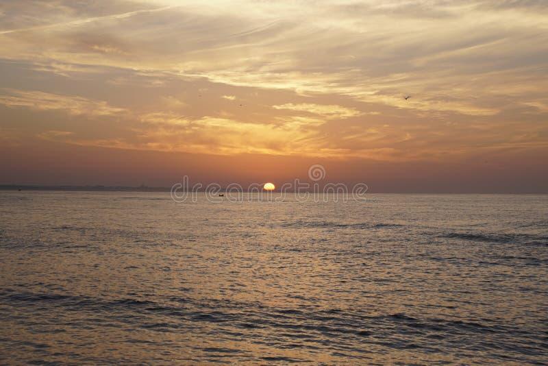 在海洋的清早 日出 明亮的颜色 有渔夫的小船 天际太阳圆盘 免版税库存照片