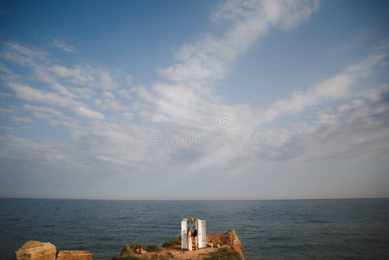 在海洋附近的室外海滩婚礼仪式,婚礼夫妇在岩石的婚礼法坛附近站立在海洋上 库存图片