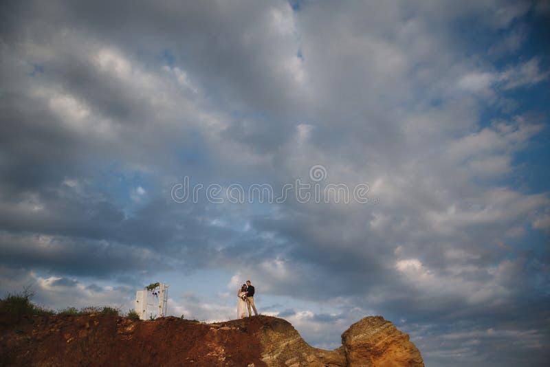 在海洋附近的室外海滩婚礼仪式,婚礼夫妇在海洋上的岩石站立 库存图片