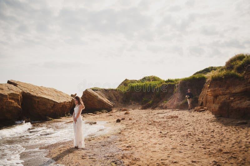 在海洋附近的室外海滩婚礼仪式,时髦的愉快的微笑的新郎来临到他的有婚礼花束的新娘 库存照片