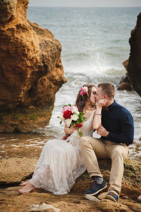 在海洋附近的室外海滩婚礼仪式,浪漫愉快的夫妇在石头亲吻在海滩 库存图片