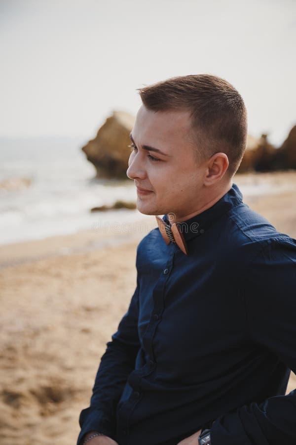 在海洋附近的室外海滩婚礼仪式,深蓝衬衣的时髦的愉快的微笑的新郎有木弓领带的 库存图片