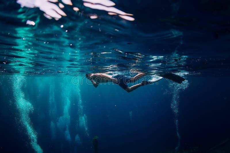 在海洋,与潜水者的水下的照片供以人员自由潜水者游泳 免版税库存照片