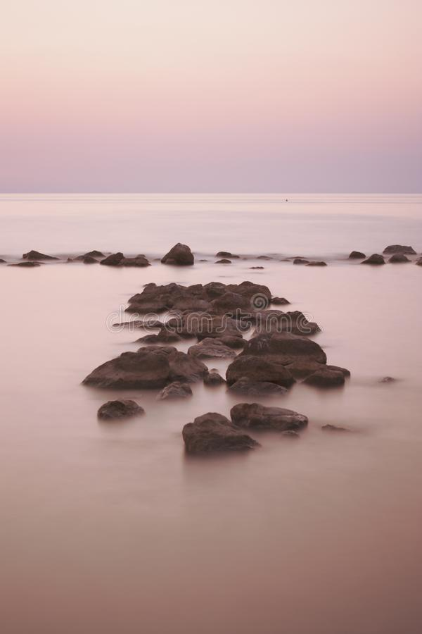 在海海滩一会儿夏天日落的岩石 库存图片