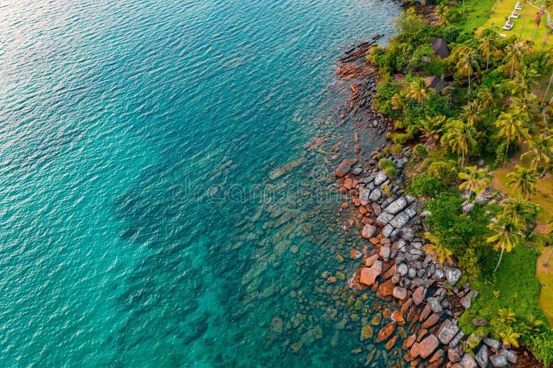 在海海滩的岩石从寄生虫角度到明显地海水 它能看到在海后的沙子 免版税库存图片