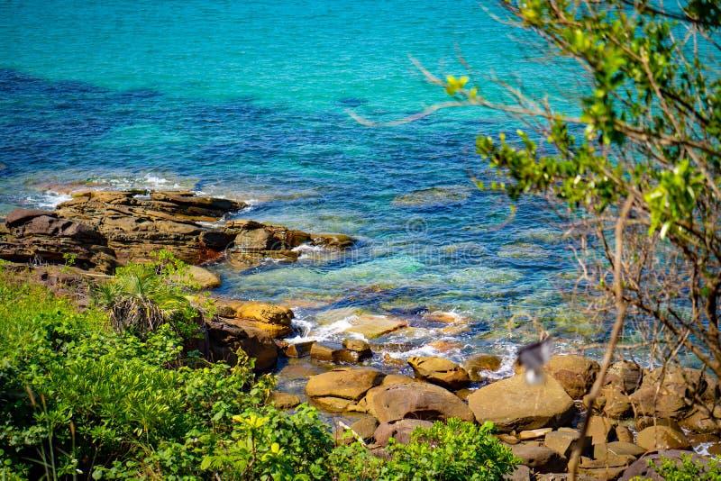 在海海滩的岩石从远透镜角度到明显地海水 它能看到在海后的沙子 库存图片