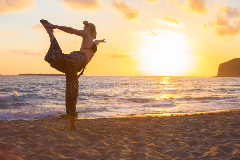 在海海滩的女子实践的瑜伽在日落图片