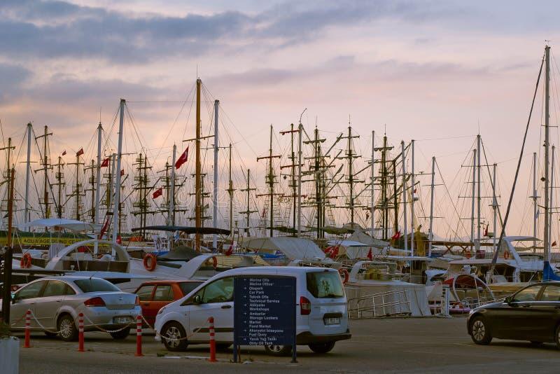 在海港的美好的日落与游艇和汽车 免版税库存图片