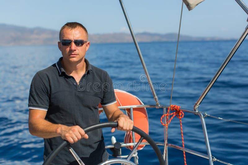 在海游艇况赛期间,舵帆船的男性船长,控制运送 免版税图库摄影