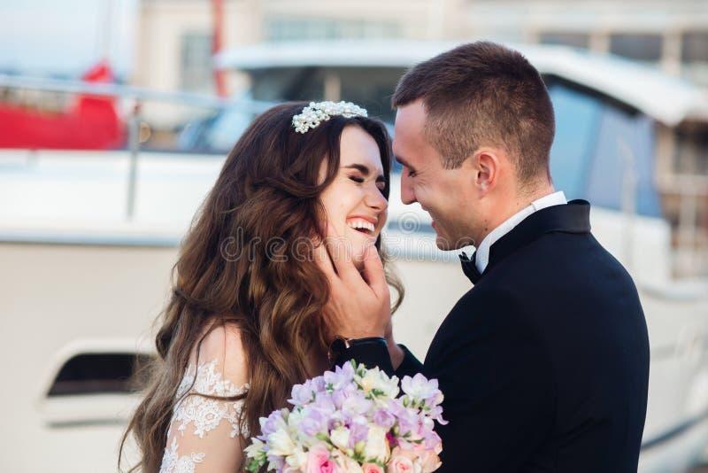在海游艇附近的美好的新娘和新郎婚礼夫妇身分 在婚礼的愉快的新婚佳偶夫妇 免版税库存图片