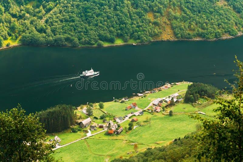 在海湾之间的船航行 在Sognefjord海湾附近的村庄没有的 免版税库存照片