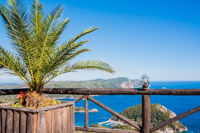 在海湾和海滩与花、棕榈树和蓝色海水的Paleokastritsa的看法在海岛科孚岛,希腊上 视图 图库摄影