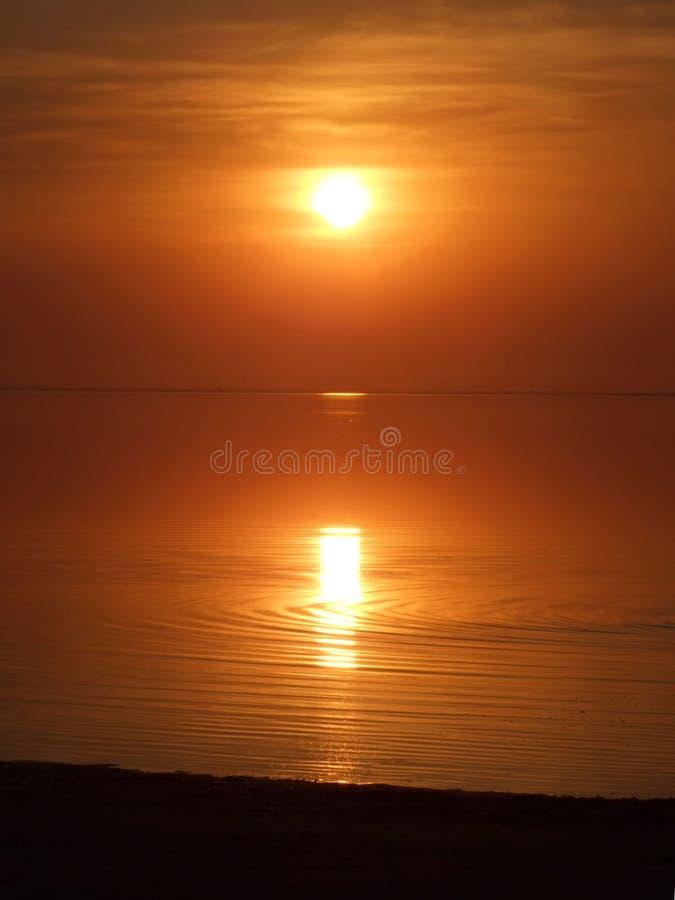 在海湾桔子日落之上 免版税库存图片