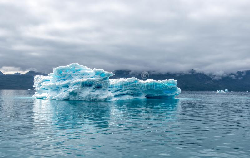 在海湾的冰山,蓝色冰山与里面清楚的蓝色颜色斑点它和充满天空的剧烈的心情在大西洋 库存图片