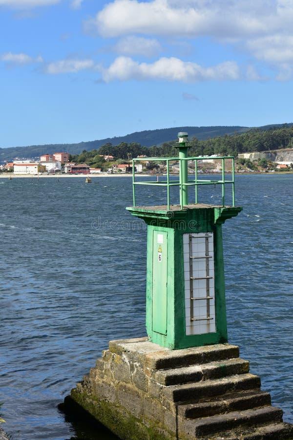在海湾的小绿色灯塔 小沿海村庄,大海 晴天,与云彩的蓝天 加利西亚,西班牙 免版税库存图片
